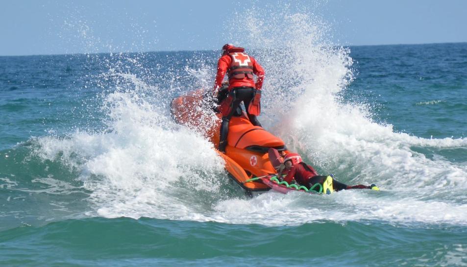 Imatge de dos socorristes de la Creu Roja amb una moto d'aigua.