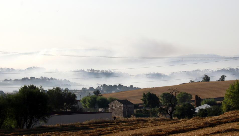 Des de Santa Coloma de Quearlt on es veu zones amb fum al fons.