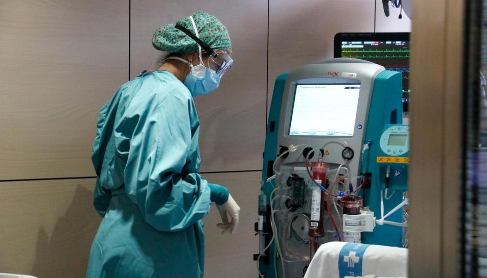 Una infermera amb una màquina per filtrar la sang d'un pacient amb covid-19 ingressat a l'UCI de Vall d'Hebron.