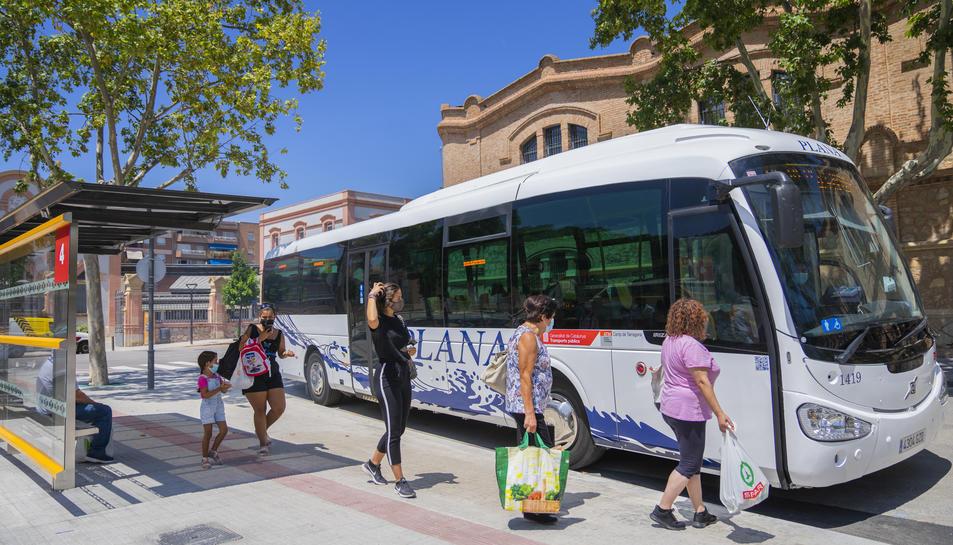 Usuaris del transport públic esperant per pujar a l'autobús a la parada Reus Centre (Passeig)
