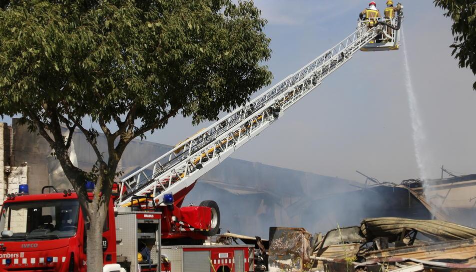 Els Bombers apagant l'incendi en unes naus de Montblanc, llançant aigua des del camió grua.