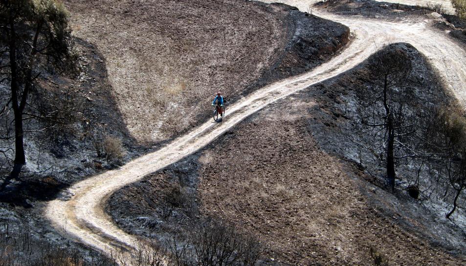 Un ciclista pujant pel camí d'accés al castell de Queralt.