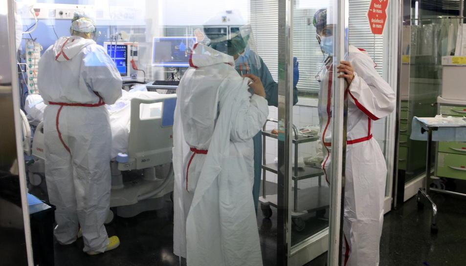 Professionals sanitàries de l'Hospital del Mar atenent un pacient ingressat a l'UCI amb covid-19.