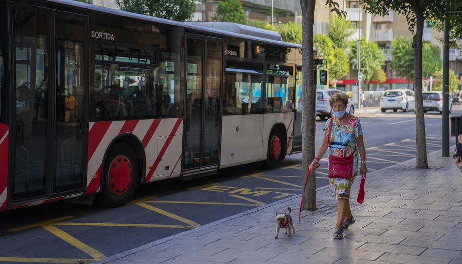 Una senyora passeja el seu gos pel centre de Tarragona mentre passa un autobús.