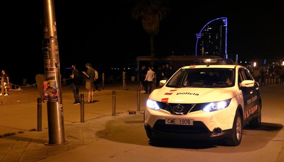 Un cotxe dels Mossos patrulla per la Barceloneta poc abans del toc de queda.