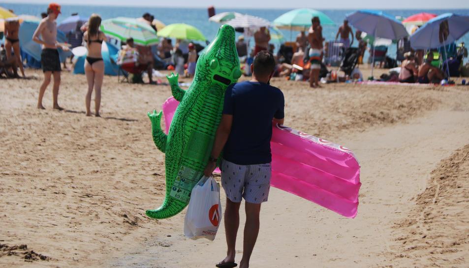 Un noi que es dirigeix a la platja de Salou (Tarragonès) amb dos flotadors.
