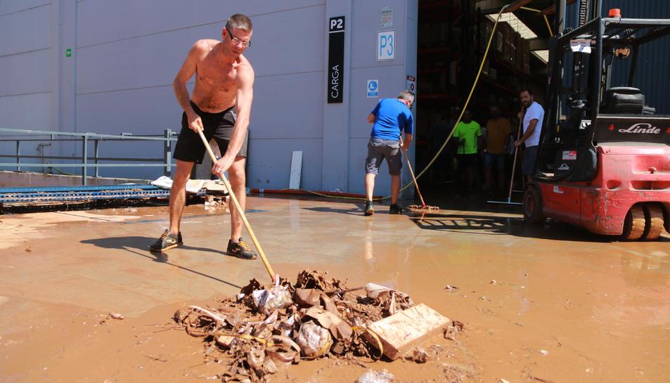 Un treballador d'una empresa de mobles de bany del polígon industrial Valldepins d'Ulldecona, durant les tasques de neteja després de l'aiguat d'aquest dimecres.