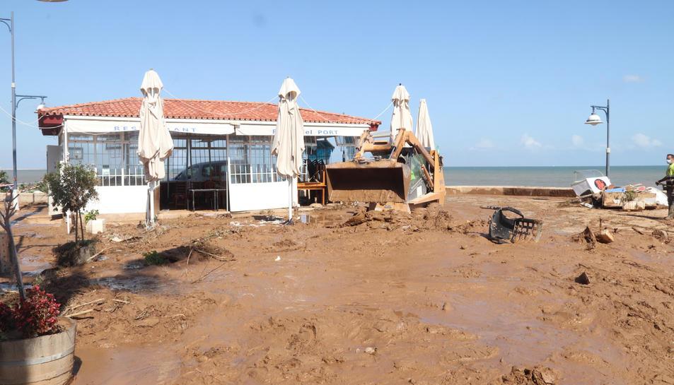 Pla obert d'un carrer de les Cases d'Alcanar, amb una màquina netejant el fang.