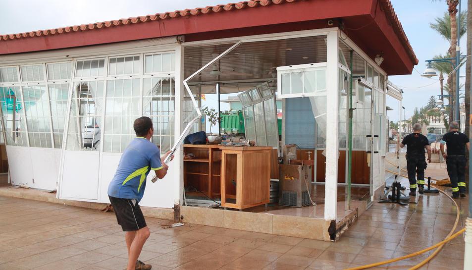 Un home mentre retira els vidres d'una guingueta a primera línia de mar d'Alcanar.