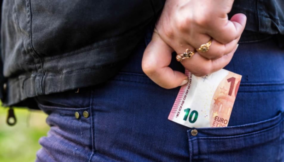 Imatge d'arxiu d'una persona ficant-se diners a la butxaca.