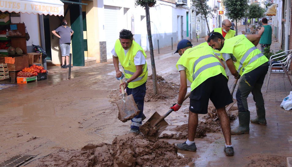 Un grup de voluntaris de l'Ametlla de Mar treballant en les tasques de neteja d'un dels carrers principals de les Cases d'Alcanar.