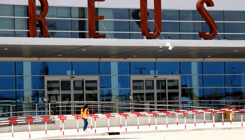 Una operària que passa per davant la nova terminal de l'Aeroport de Reus.