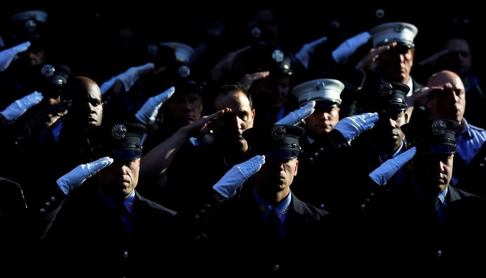 Integrants del Departament de Bombers de Nova York guarden un minut de silenci en honor als morts durant l'11 de setembre de 2021, aquest dissabte a Nova York