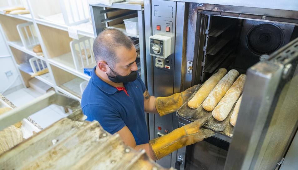 Noel Urbano, de la Pastisseria Noel, ubicada al carrer de Florenci Vives, posant al forn unes barres de pa.