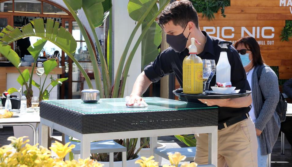 Un cambrer d'un restaurant de Sitges netejant la taula entre serveis d'aperitius.