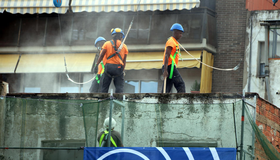 Operaris treballant en l'enderroc d'un edifici.