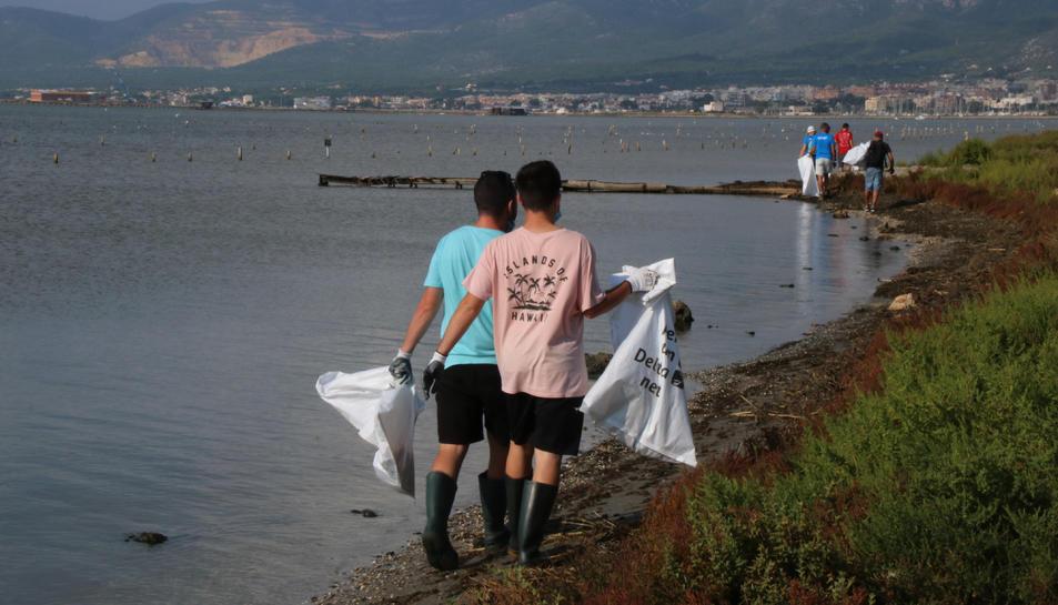 Dos voluntaris amb bosses netejant en l'acció feta a la badia dels Alfacs.