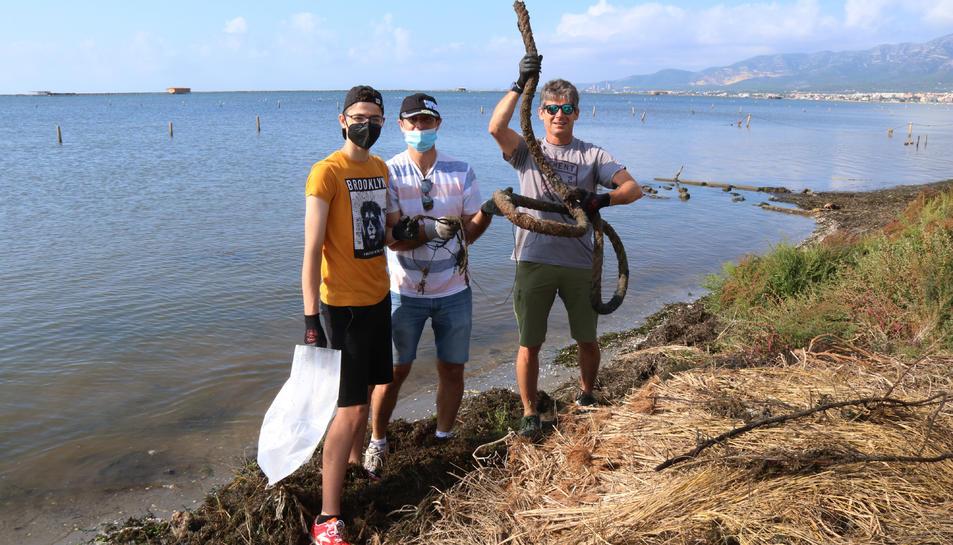 Tres voluntaris mostrant un dels residus recollits durant l'acció feta a la badia dels Alfacs.