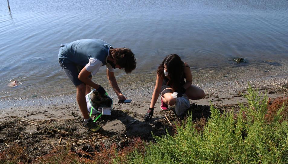 Dos voluntaris fotografiant residus durant l'acció feta a la badia dels Alfacs.