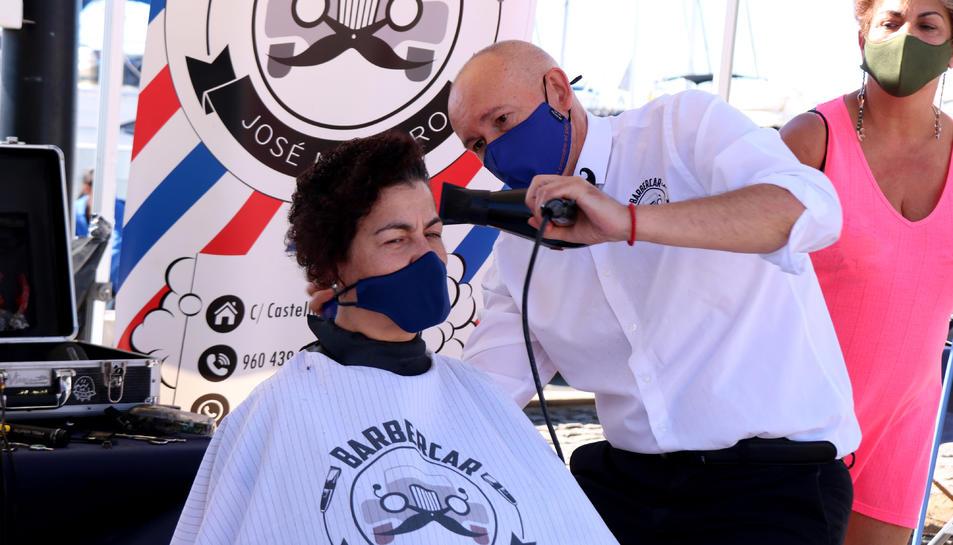 """Pla tancat d'un perruquer eixugant el cabell d'una dona que ha participat en la cinquena edició de la campanya """"Deixa't prendre el pèl"""" a Cambrils."""