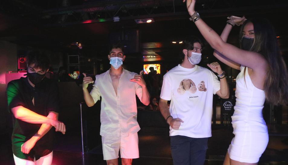Pla mig d'un grup de joves que balla amb mascareta a la pista de la discoteca Flashback de Salou.
