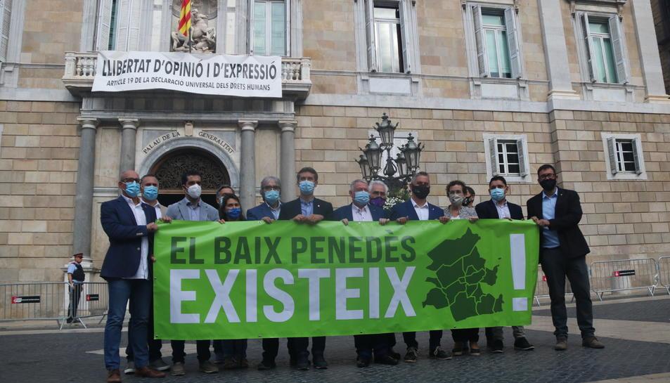 Pla obert dels 14 alcaldes del Baix Penedès mostrant una pancarta davant el Palau de la Generalitat.