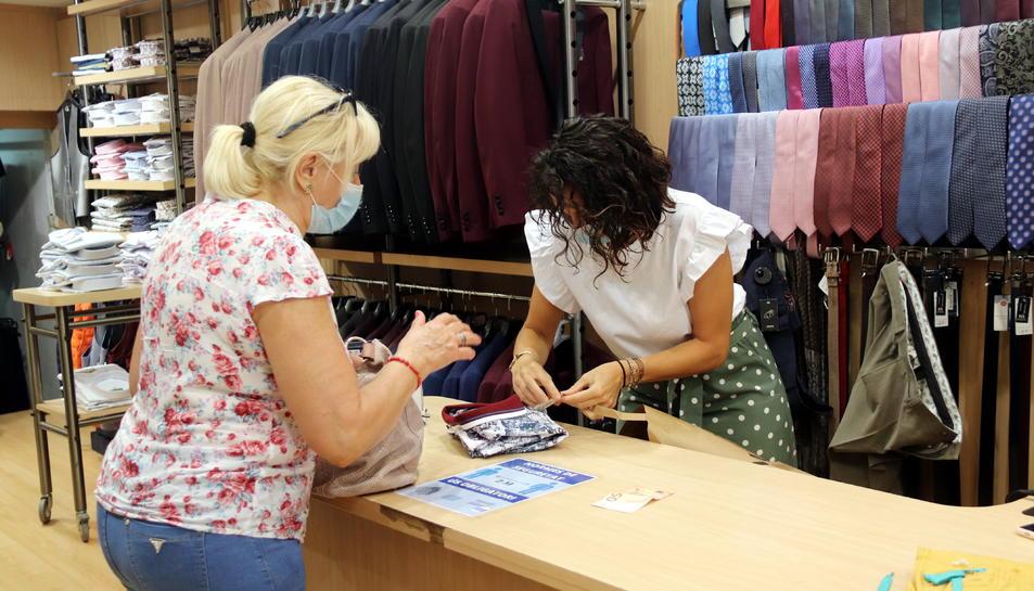 Una dependenta i una clienta en una botiga de roba del carrer Monterols de Reus.