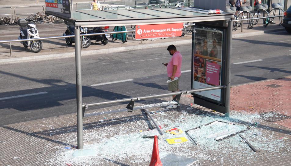 Una marquesina d'autobús pròxima a la plaça Espanya amb els vidres trencats.