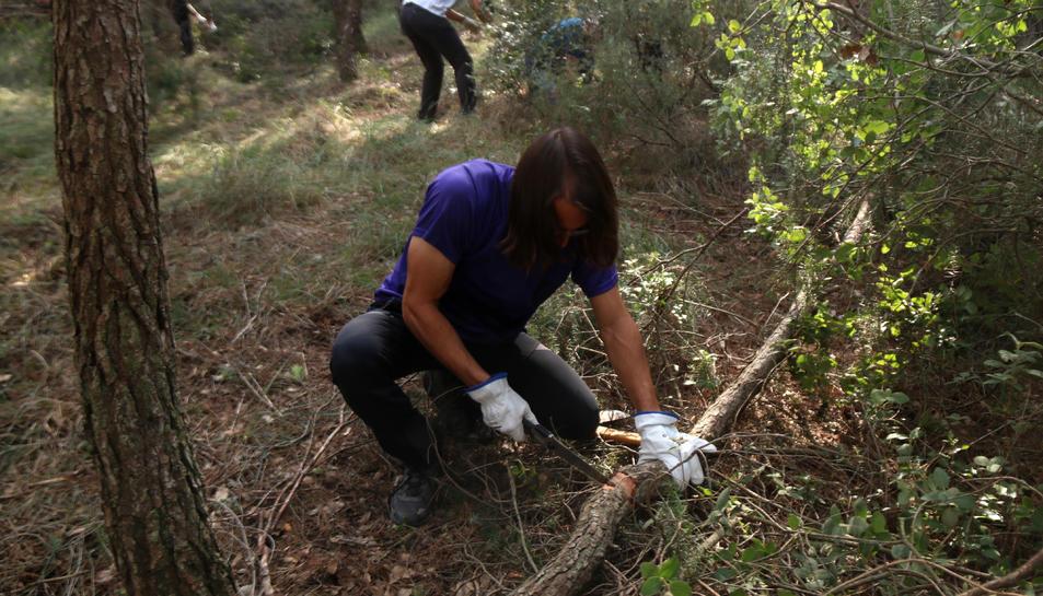 Un dels voluntaris tallant un tronc en l'acció de neteja organitzada per la plataforma Revifem Queralt al terme municipal d'Argençola (Anoia)