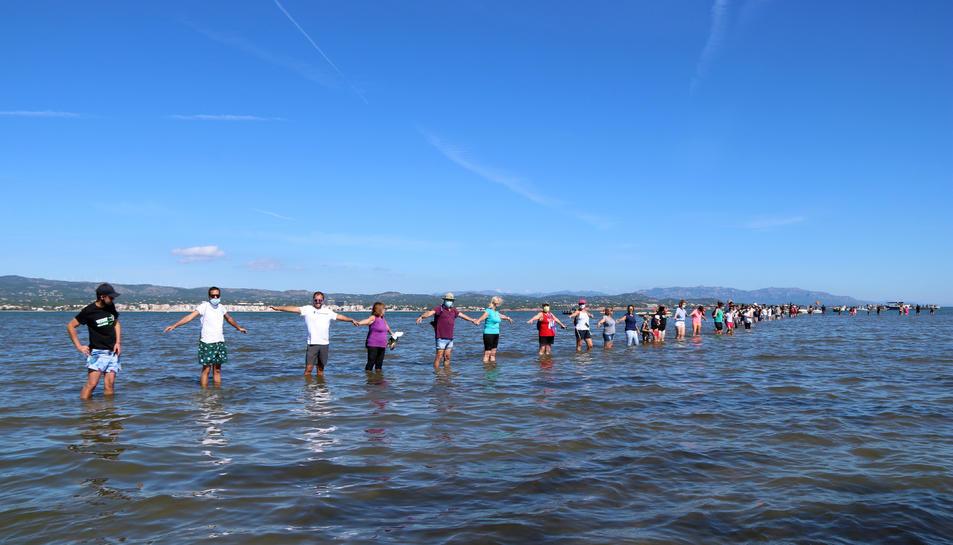 Els participants fent la cadena humana a la badia del Fangar, a l'Ampolla (Baix Ebre), per denunciar la regressió que pateix el delta de l'Ebre.