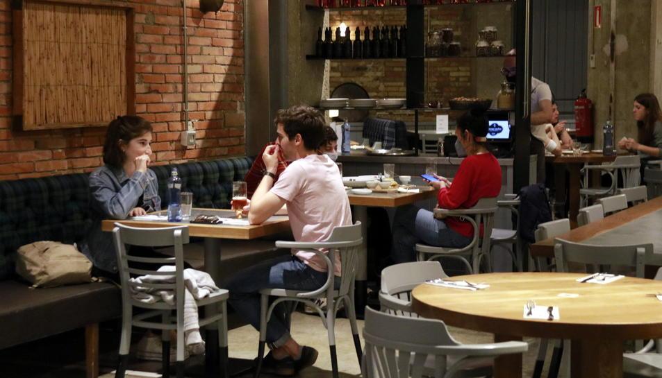 Pla obert de diverses taules amb comensals dins d'un restaurant.