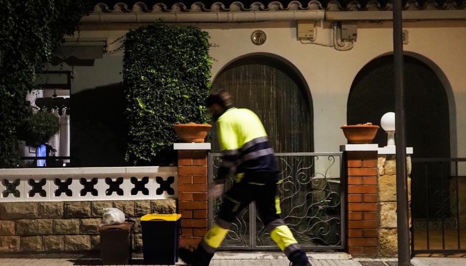 Pla general d'un operari recollint els residus a la porta d'un habitatge de Móra la Nova.