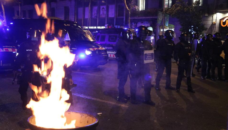 Agents dels Mossos d'Esquadra al costat d'una paperera en flames durant els aldarulls posteriors a una manifestació dels CDR pel quart aniversari de l'1-O.