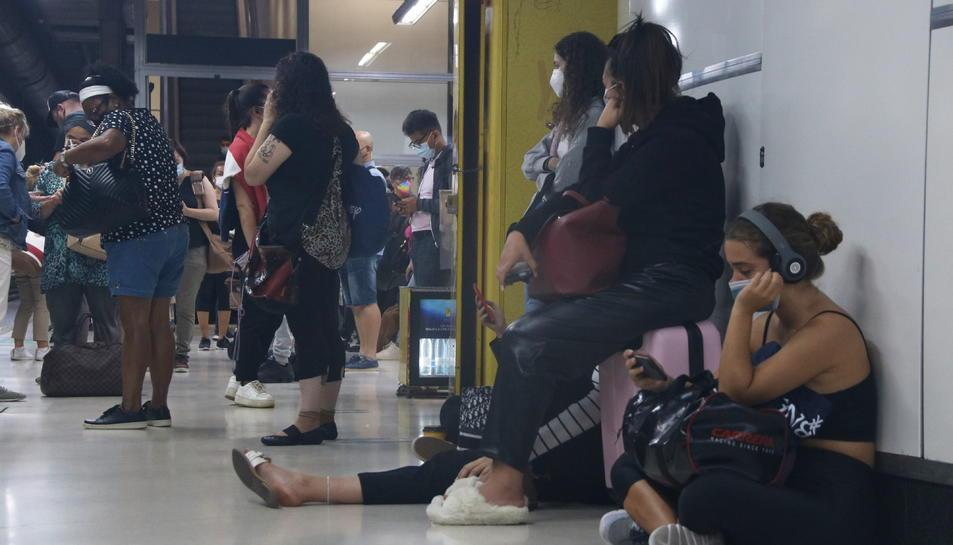 Pla tancat de diversos passatgers de Renfe esperant el seu tren a una de les andanes de l'estació de Sants.