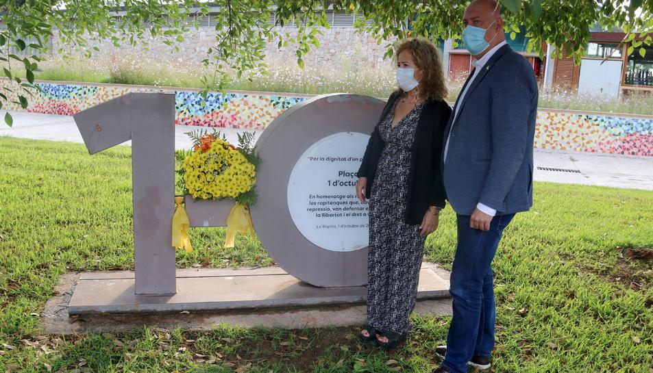 Pla sencer de l'alcalde de la Ràpita, Josep Caparrós, i la coordinadora local de l'ANC, Mariona Gairí, durant l'ofrena floral al monòlit commemoratiu de l'1-O.