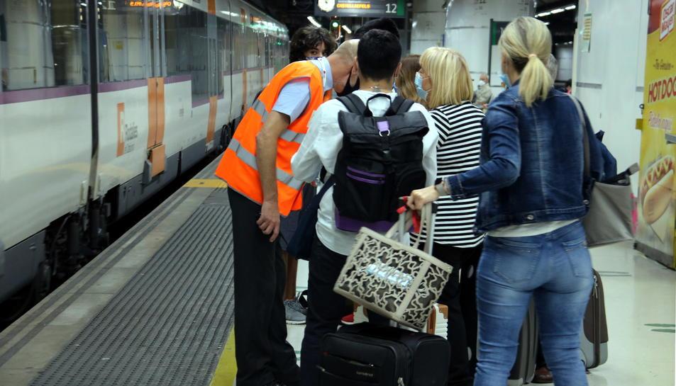 Personal de l'estació de Barcelona-Sants a l'andana informant als afectats per la vaga dels maquinistes.