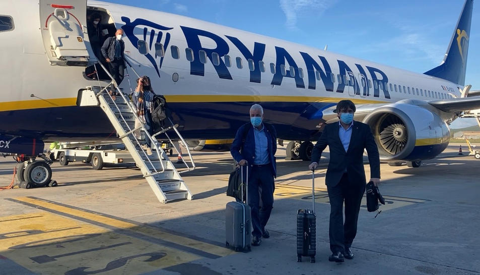 L'expresident Carles Puigdemont i l'exsenador Jami Matamala, sortint de l'avió de Ryanair que els ha portat des de Brussel·les fins a l'Alguer.