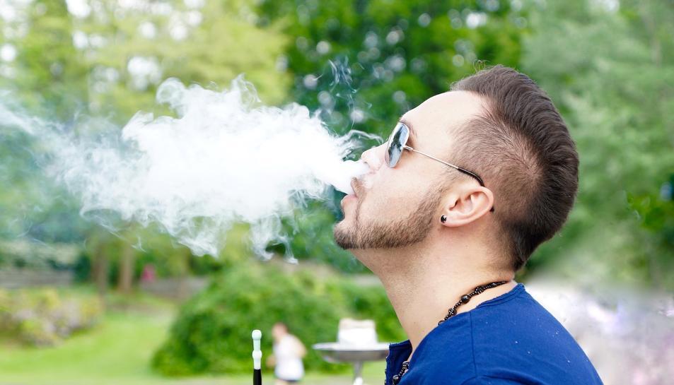 Imatge de recurs d'un noi fumant d'una pipa d'aigua.