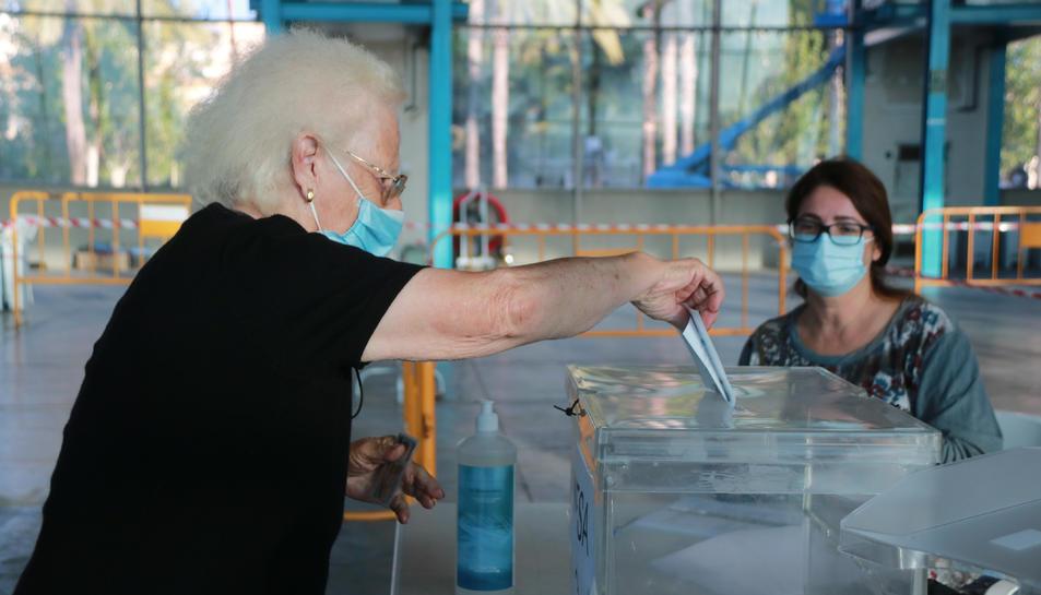 Pla mitjà d'una dona gran que exerceix el seu dret a vot.