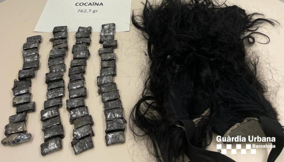 Diversos embolcalls de cocaïna al costat d'una perruca.