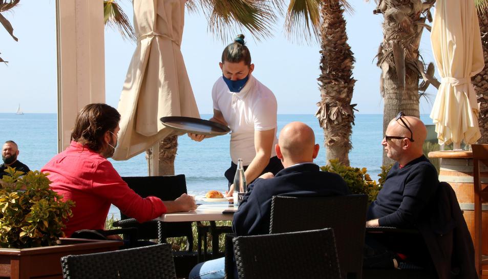 Pla tancat d'un cambrer servint una taula en una terrassa de Sitges.