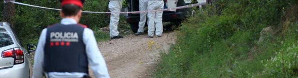 Plano general de la policía científica equipándose para acceder en el lugar donde se ha encontrado un cuerpo calcinado al lado del Pantano de Foix. En primer plano, un agente de los Mossos D'Esquadra. Imagen del 5 de mayo de 2017