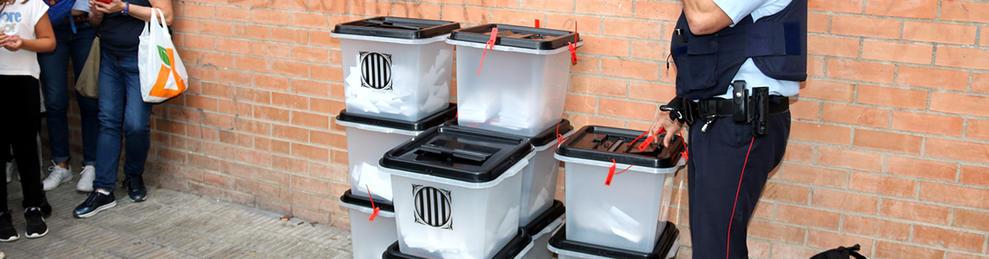 Un agents dels Mossos inspeccionant unes urnes requisades l'1 d'octubre passat.