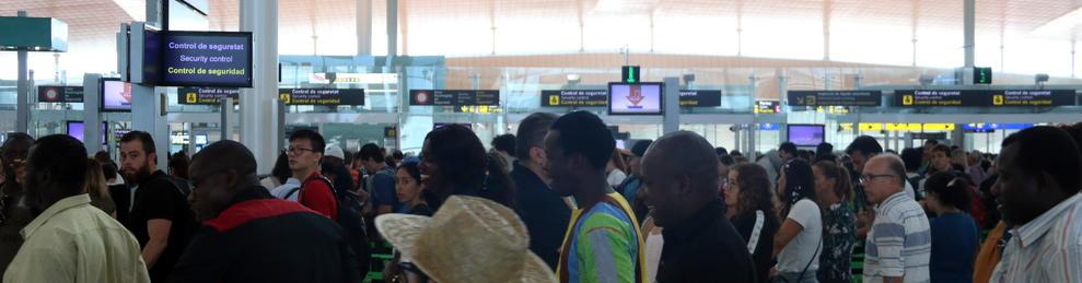 Diverses persones fent cua al control de seguretat de sortida de la T-1 de l'aeroport de Barcelona.