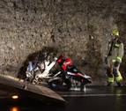 Els serveis d'emergències retiren la moto que ha quedat destrossada després de l'impacte