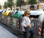 Una mujer que abre un contenedor de basua para tirar residuos.