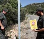 Dos efectivos de los Agents Rurals a punto de colocar un cartel que indica que está prohibido acceder a la sierra del Montsec.