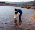 Plano general de un técnico de la CHE toman una muestra en superficie en una pantano de la cuenca del Ebro.