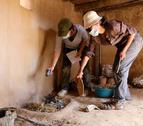 Plano abierto de dos investigadoras del ICAC analizando una chimenea recreada.