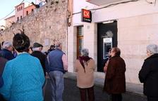 Alguns veïns de Rasquera davant del caixer automàtic del BBVA que no funciona on han llençat un ou. Imatge del 14 de febrer de 20'17 (horitzontal)